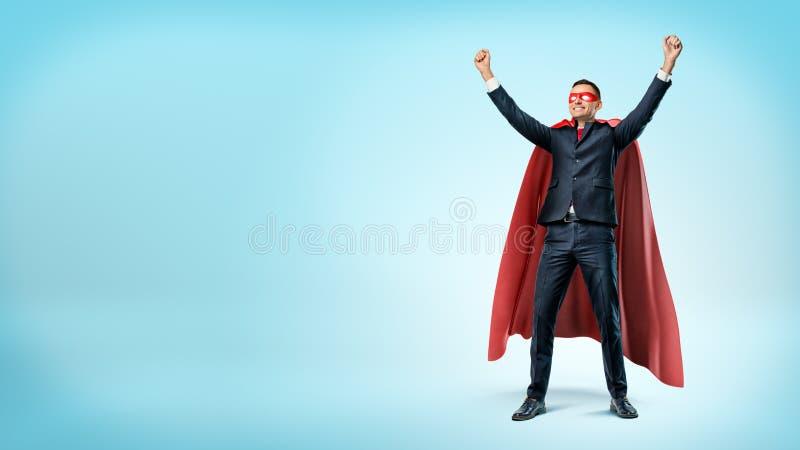 在站立在蓝色背景的胜利姿势的超级英雄红色海角的一个愉快的商人 免版税库存照片