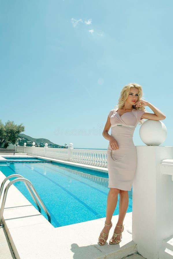 在站立在豪华旅馆前面的红色礼服的美好的典雅的女性时装模特儿 库存照片