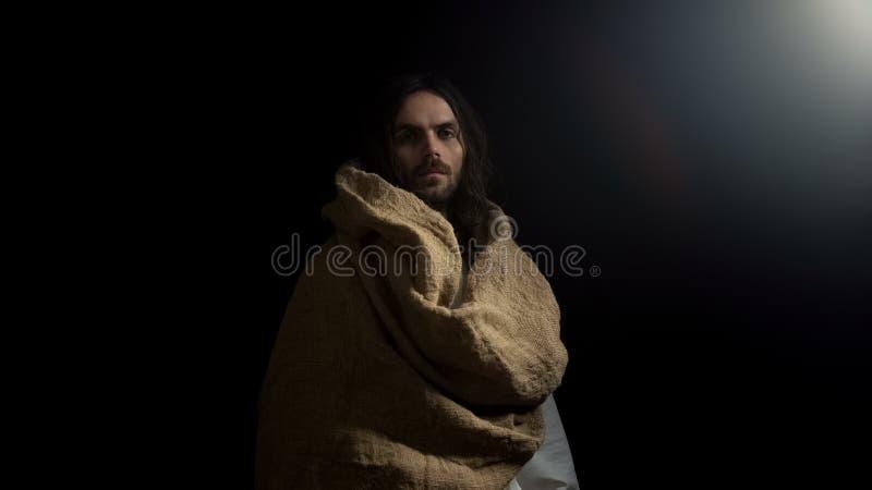 在站立在黑暗中和调查照相机,神祝福,福音书的长袍的男性 免版税库存照片