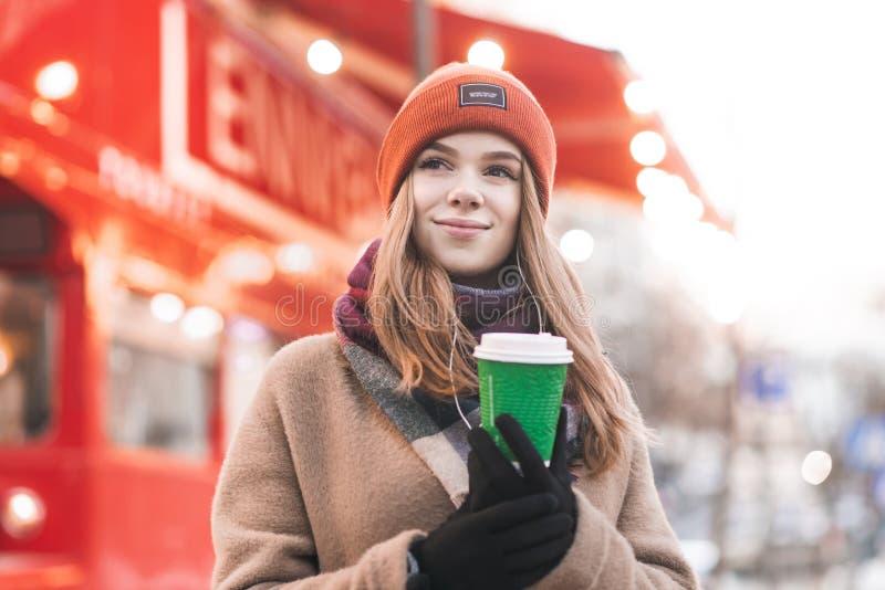 在站立外面在与在旁边一杯咖啡的一个冷的春日的衣服暖和的画象青少年的女孩附近在他的手和神色上  免版税库存照片