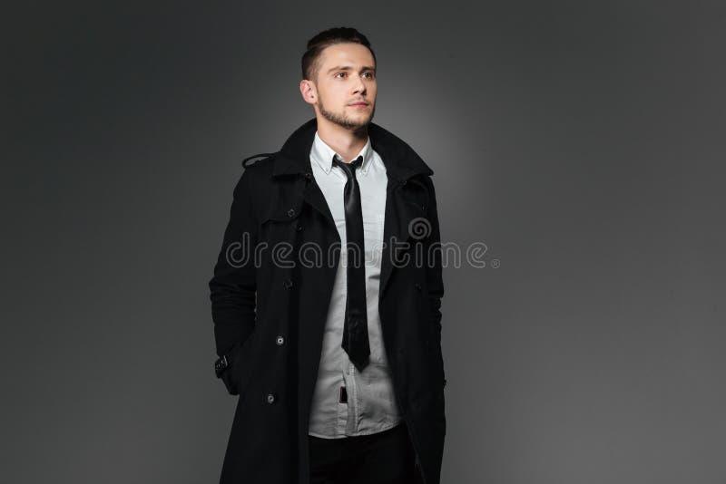 在站立用在口袋的手的黑外套的商人 库存照片