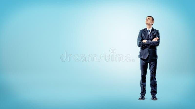 在站立用手的蓝色背景的一个商人横渡了若有所思 免版税库存照片