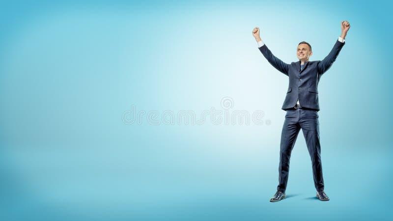 在站立用手的蓝色背景的一个愉快的微笑的商人在胜利行动上升了 图库摄影