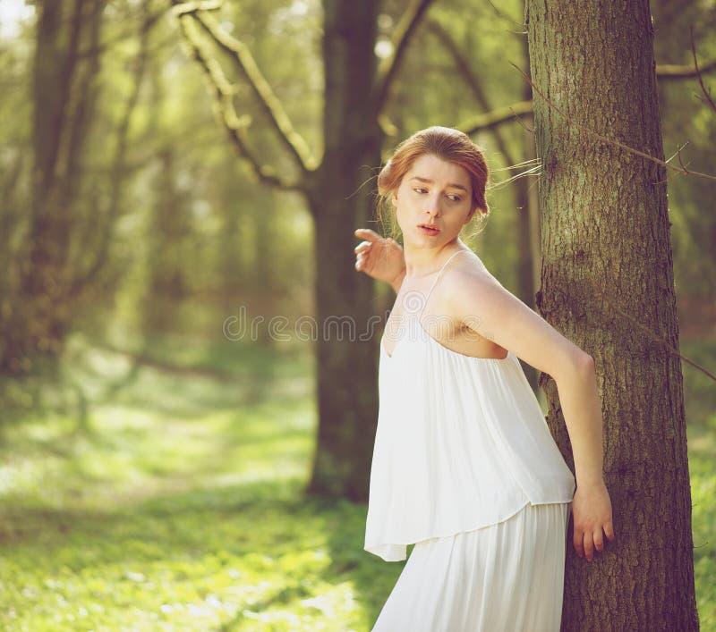 在站立白色的礼服的美好的时装模特儿户外 免版税图库摄影