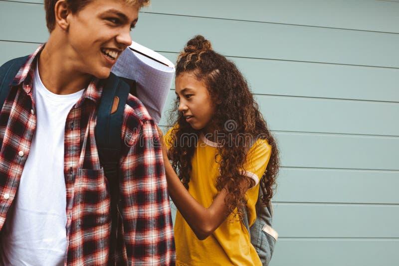 在站立的书的十几岁的女孩文字户外 库存照片