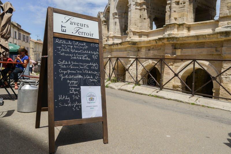 在竞技场和罗马圆形露天剧场,阿尔勒,普罗旺斯,法国旁边的餐馆菜单 库存图片