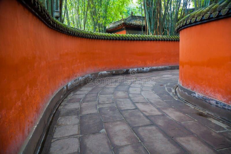 在竹子围拢的红色墙壁之间的段落,成都,瓷 库存图片