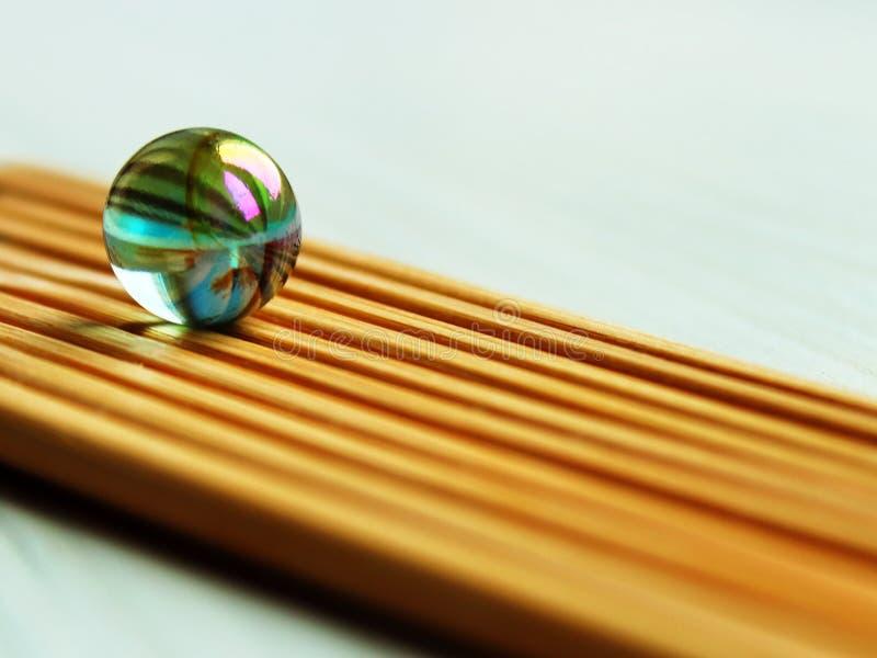 在竹棍子有一个角度背景的玻璃球 免版税库存照片