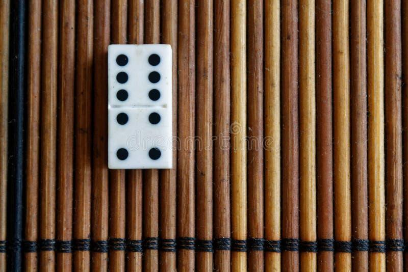 在竹棕色木桌背景的多米诺片断 被设置-四个- 5个小点的多米诺 免版税库存照片