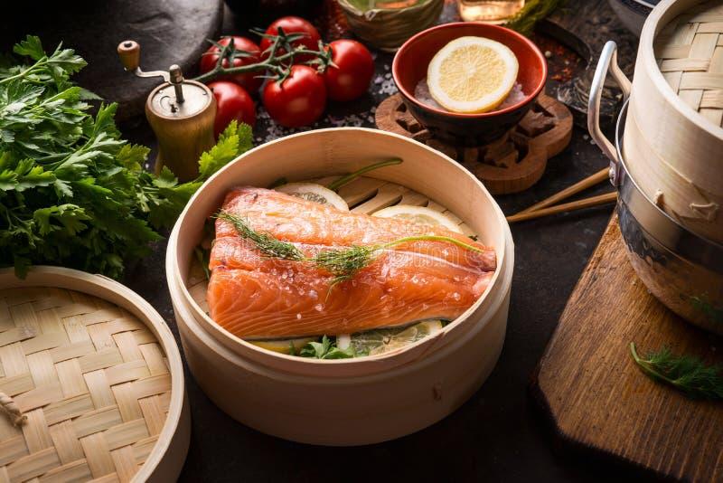 在竹火轮的未加工的三文鱼内圆角在与成份和工具的黑暗的土气厨房用桌上 健康吃和烹调 ?? 库存照片