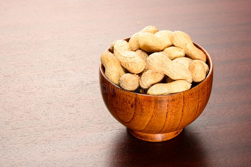 ?? 在竹碗的干燥坚果在棕色木桌上 免版税图库摄影
