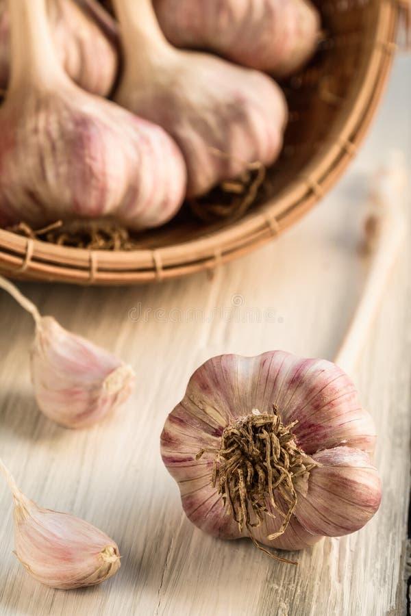 在竹篮子的大蒜在白色木背景 免版税库存照片