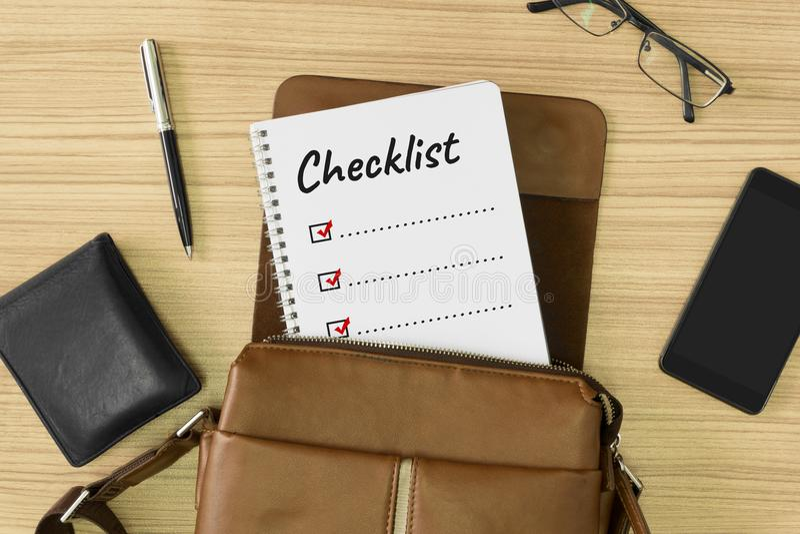 在笔记本写的清单词被安置在人` s皮包里面 免版税库存照片