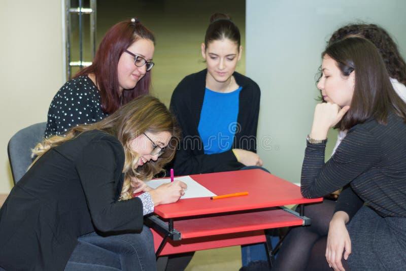 在笔记本和队合作会议的女孩文字开始概念 学习的女性变化年轻人 免版税库存图片