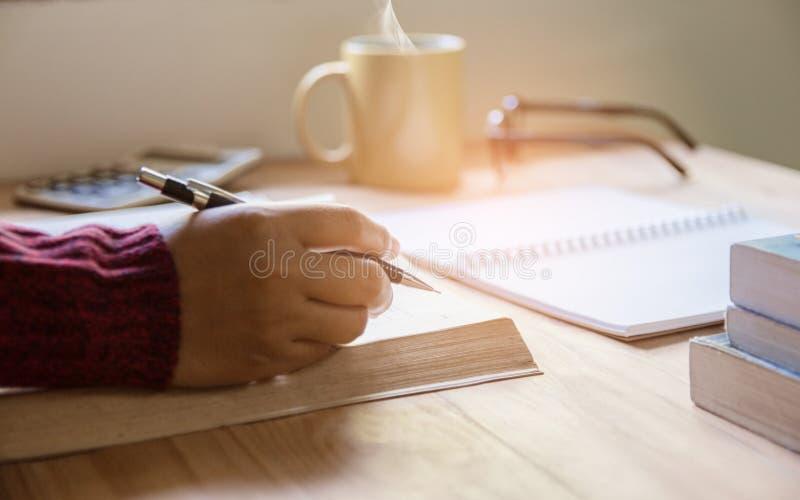 在笔记本在家区域的妇女右手文字在早晨 免版税库存图片