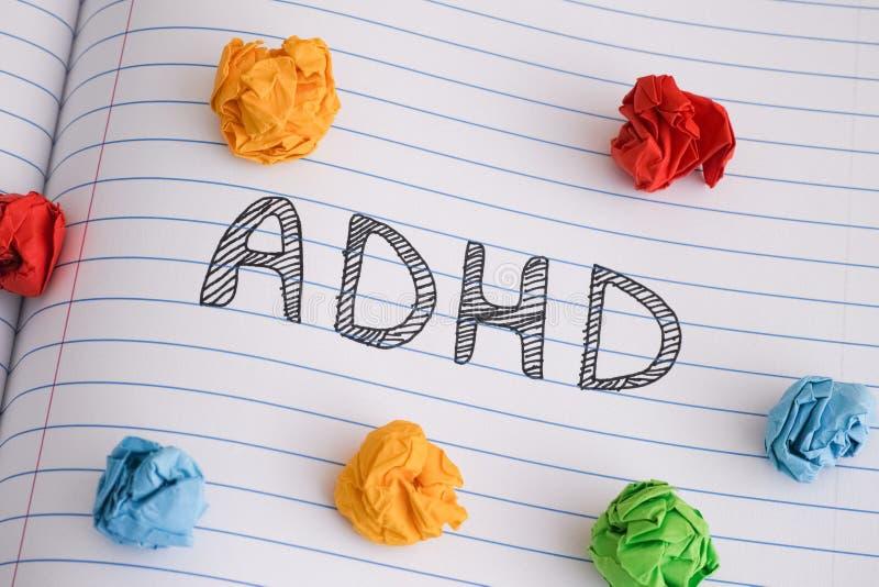 在笔记本板料的简称ADHD与对此的一些五颜六色的压皱纸球 免版税库存图片
