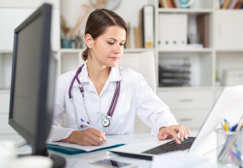 在笔记本电脑上填写医疗表格的女医生 库存照片