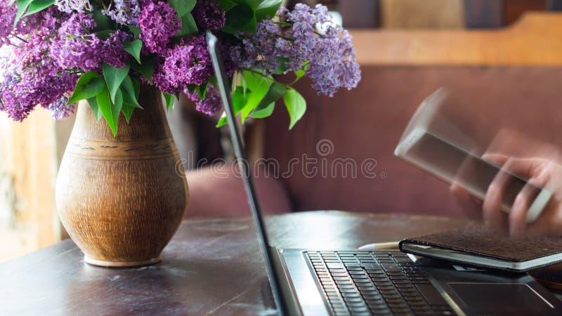 在笔记本电脑上工作的女人手里拿着智能手机 免版税图库摄影