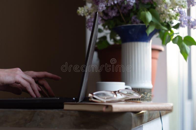 在笔记本电脑上工作的女人,拿着一束紫丁香 免版税库存照片