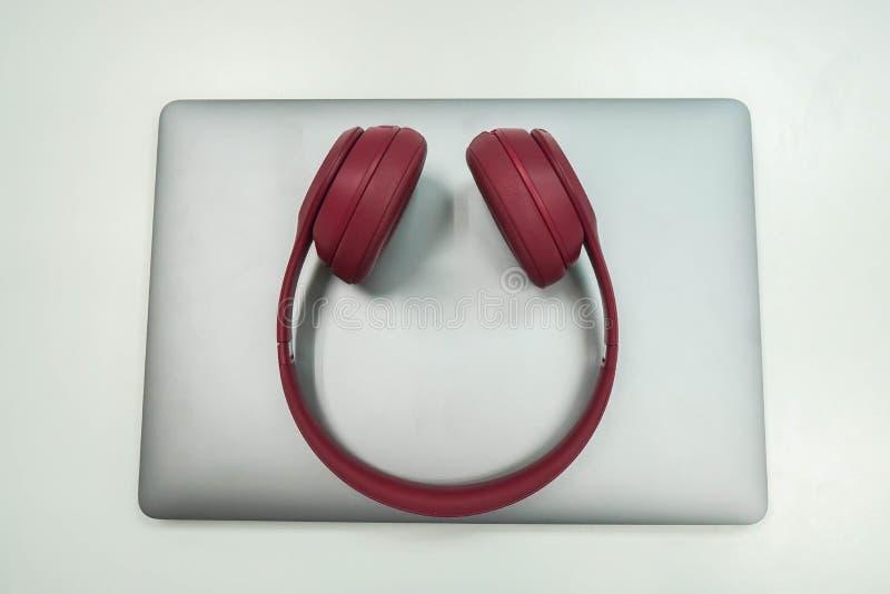 在笔记本电脑的被隔绝的笔记本逗人喜爱的桃红色无线耳机在工作场所 库存图片