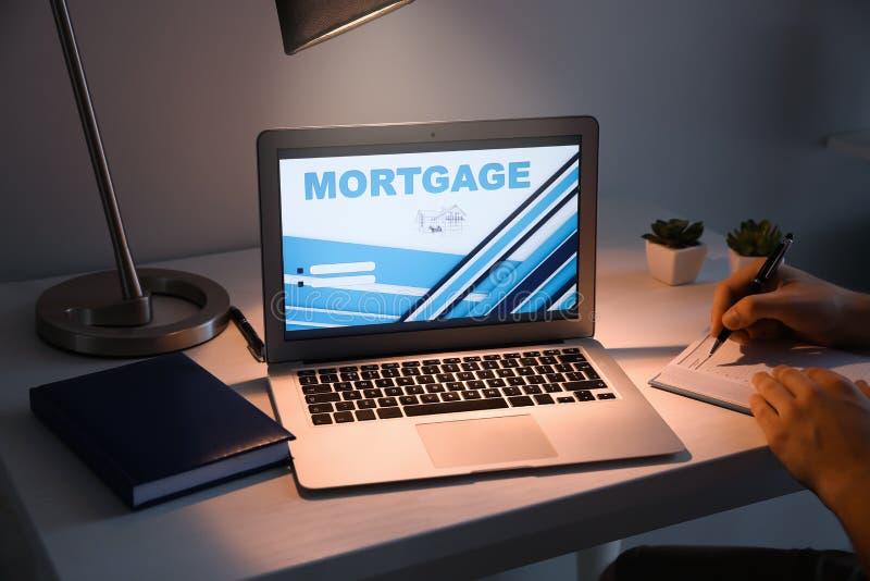 在笔记本的人文字在有联机服务开放页的膝上型计算机附近抵押贷款付款的在桌上 免版税库存照片