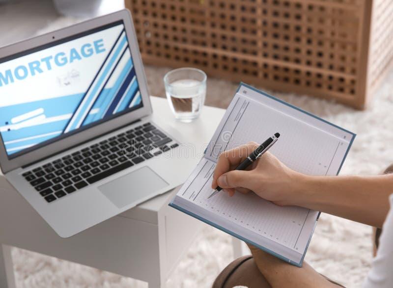 在笔记本的人文字在有联机服务开放页的膝上型计算机附近抵押贷款付款的在桌上 库存照片