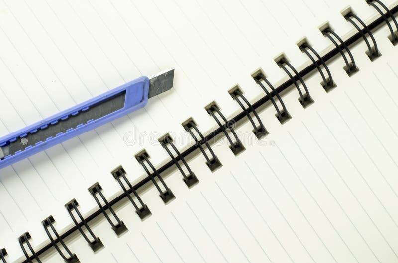在笔记本的切削刀 库存照片