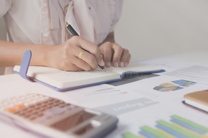 在笔记本的商人文字在木桌,人们上记录从计算器计算的帐户数据 图库摄影