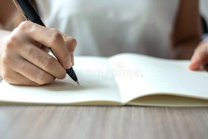 在笔记本的女实业家文字在办公室,妇女与署名的候宰栏的手在纸报告 企业计算器概念货币 库存图片