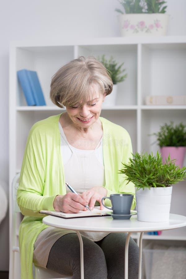 在笔记本的微笑的妇女文字 免版税库存图片