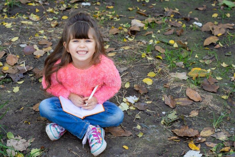 在笔记本的滑稽的儿童文字使用笔和微笑 四岁哄骗坐草, 免版税图库摄影