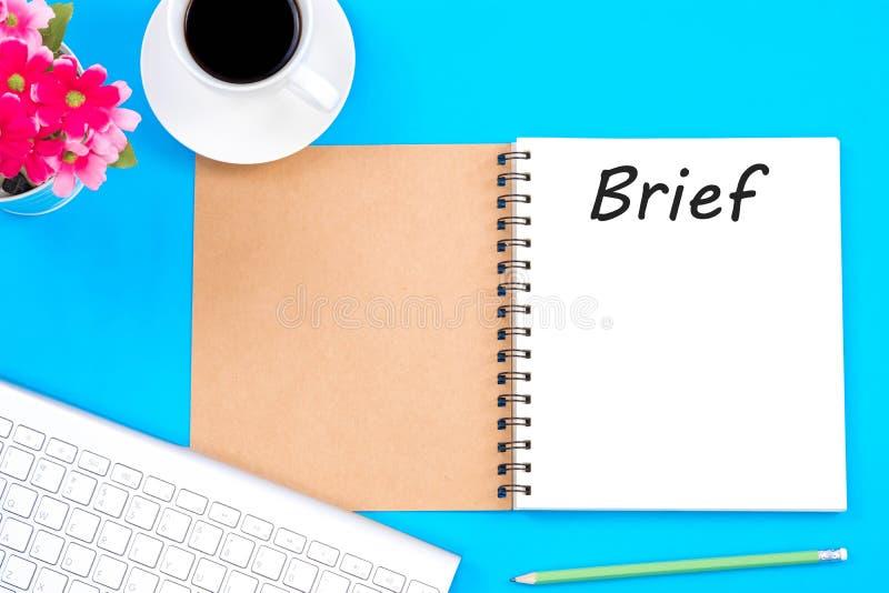 在笔记本的简要的词有玻璃、铅笔和咖啡杯的在木桌上 到达天空的企业概念金黄回归键所有权 图库摄影