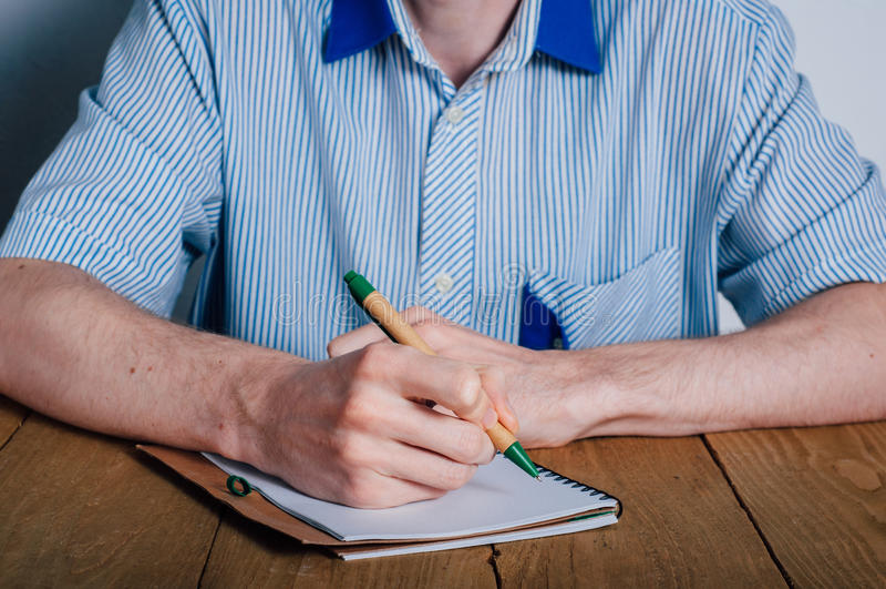 在笔记本的年轻人文字 图库摄影
