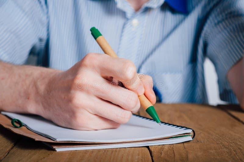 在笔记本的年轻人文字 库存照片