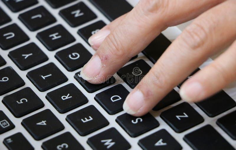 在笔记本键盘安置的手指 免版税库存照片