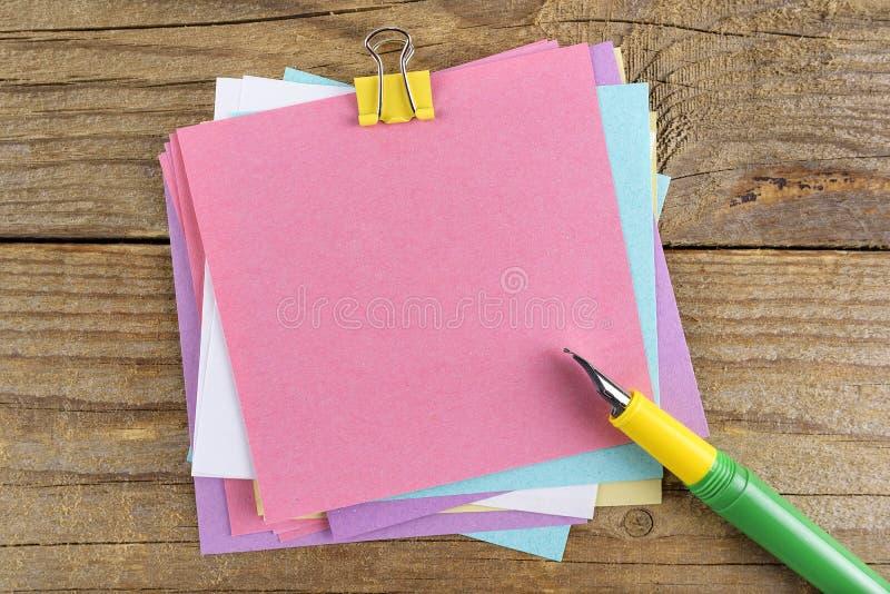 在笔记本附近的色的贴纸在老木桌上 图库摄影
