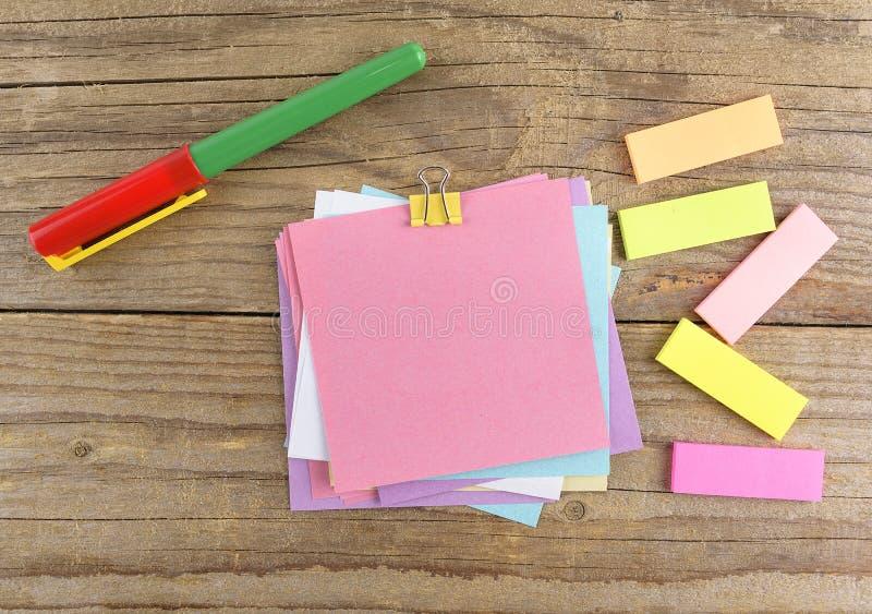 在笔记本附近的色的贴纸在老木桌上 免版税库存图片