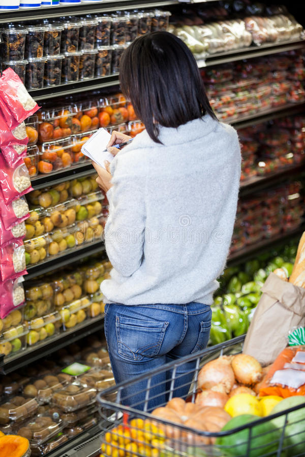 在笔记薄的妇女文字,当购物杂货时 免版税库存图片