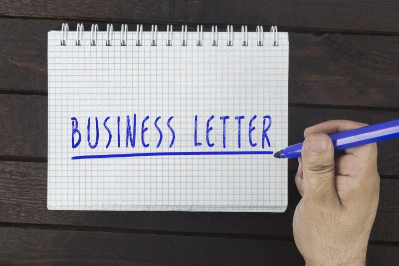 在笔记薄的手文字:商业函件 免版税库存图片