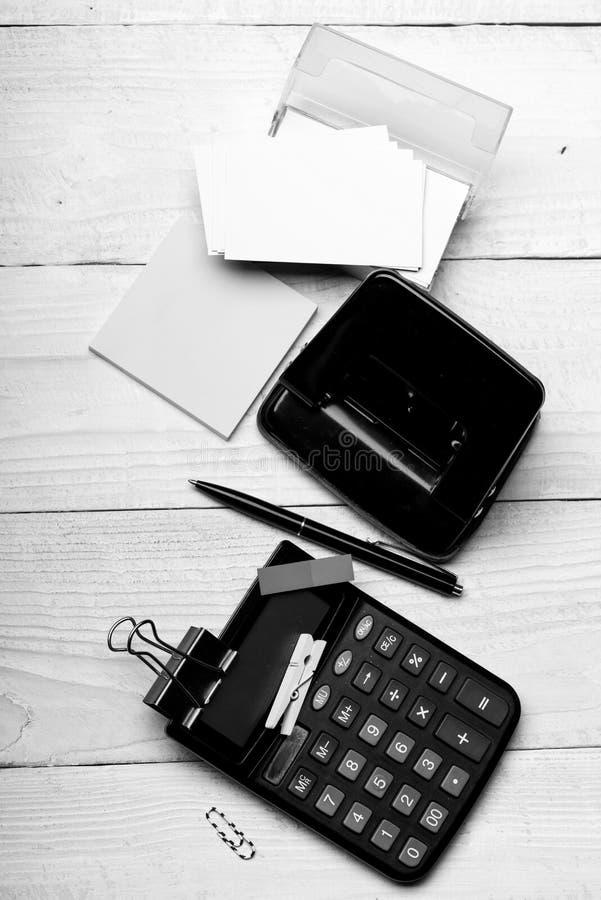 在笔附近的打孔器在白色木背景 企业想法概念 文具和计算器 免版税库存照片