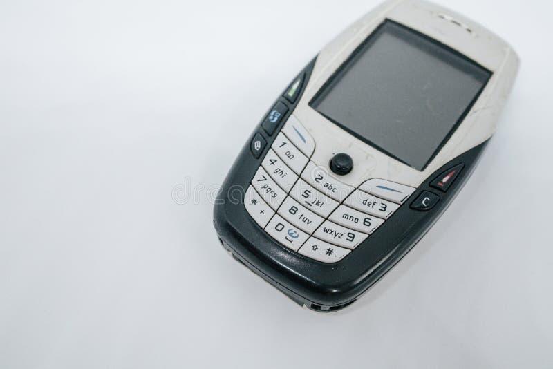 在第二代的传统手机与键盘按钮和微型黑白显示器由白色孤立冲切了backg 免版税图库摄影
