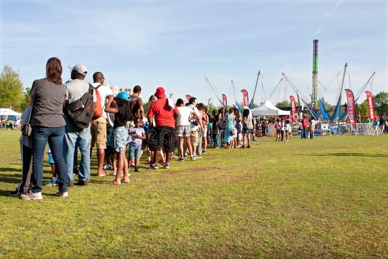 在等待亚特兰大节日乘驾的长行的家庭立场 免版税库存图片
