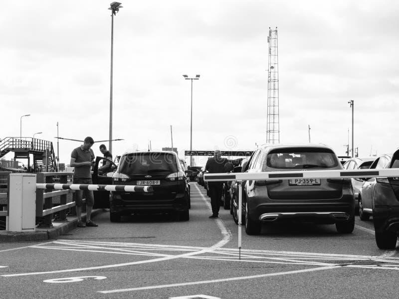 在等待在渡轮的汽车附近的人们搭乘 免版税库存照片