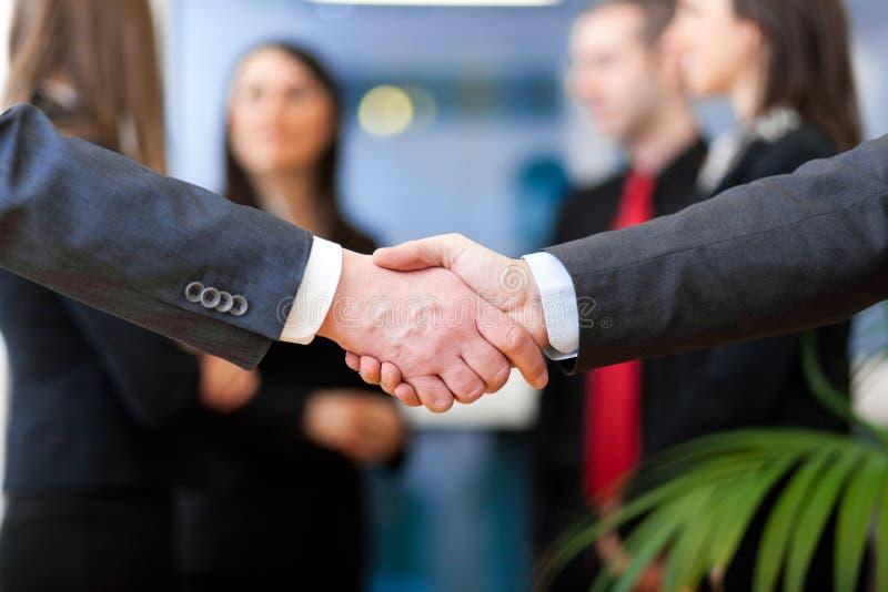 在签署的合同的商务伙伴握手的图象 免版税图库摄影