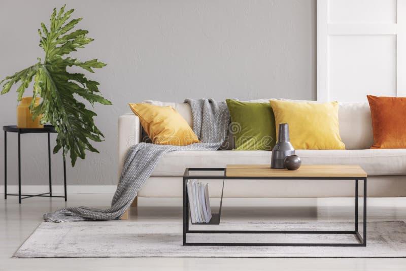 在简单的木咖啡桌上的陶瓷花瓶在有大舒适的长沙发的时髦的客厅有五颜六色的枕头的,真正的照片wi 免版税库存照片