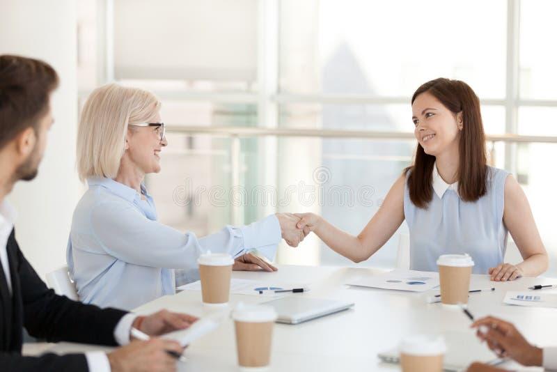 在简报期间的微笑的不同的同事握手在办公室 免版税库存照片