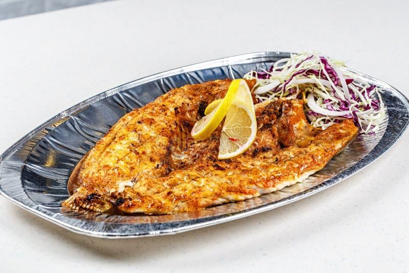 在箔板材的烤海鲷鱼服务用柠檬和花椰菜 图库摄影