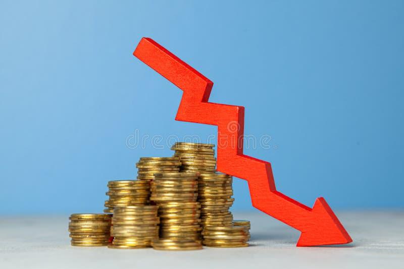 在箭头和堆硬币下 减税或下跌的赢利的概念在事务 库存照片