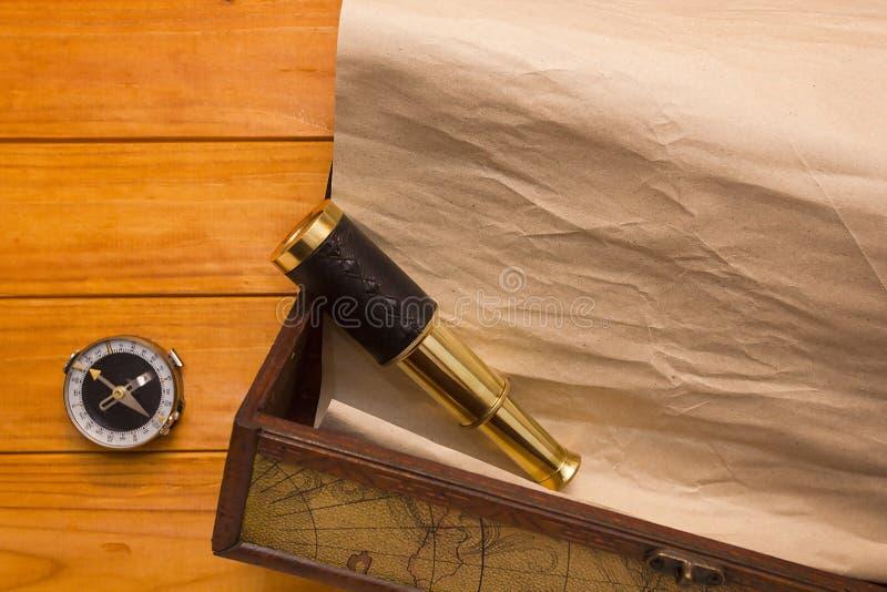 在箱子、望远镜和指南针的纸卷 图库摄影