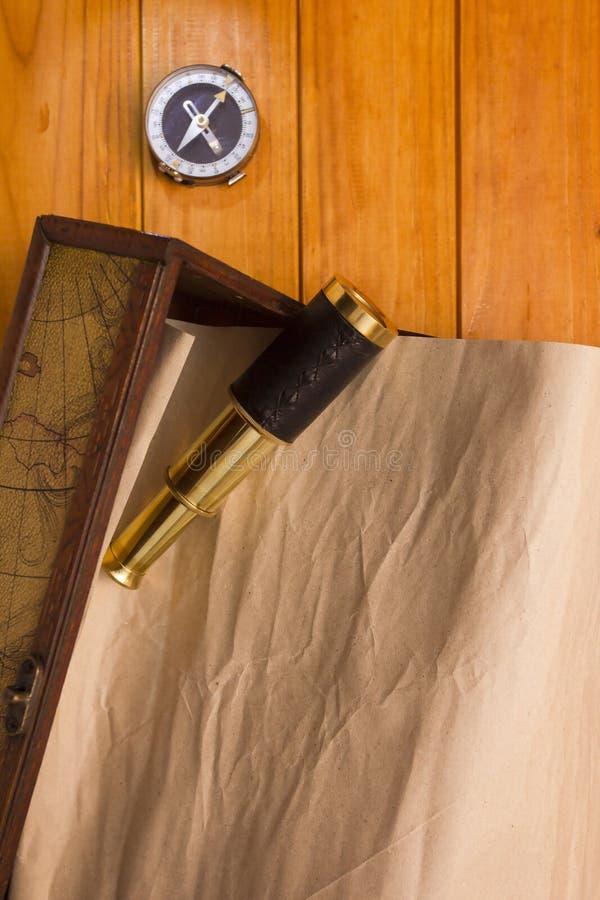 在箱子、望远镜和指南针的纸卷 库存照片